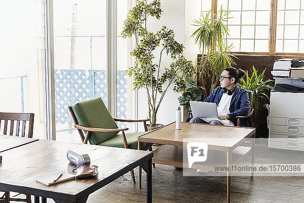 Männlicher japanischer Berufstätiger  der an einem Tisch in einem Raum für Zusammenarbeit sitzt und einen Laptop-Computer benutzt.