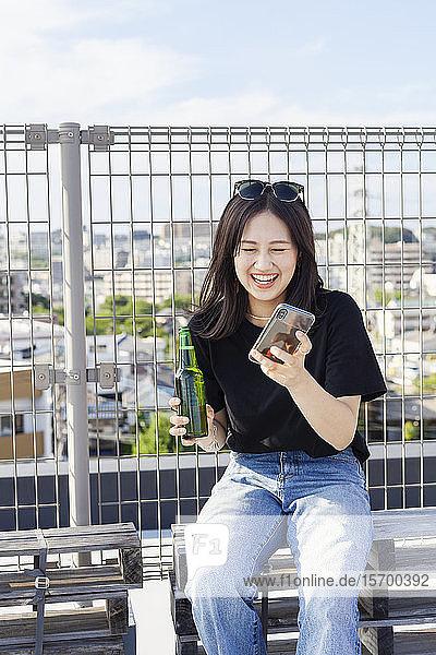 Junge Japanerin  die in einer städtischen Umgebung auf einem Dach sitzt und ein Mobiltelefon benutzt.