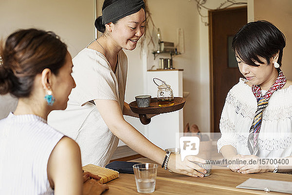 Japanerin  die zwei weibliche Kunden in einem vegetarischen Café bedient.