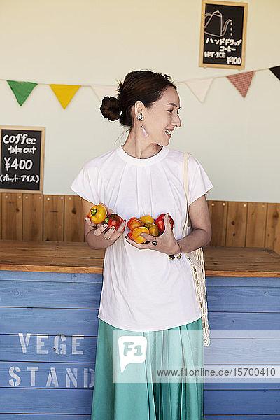 Lächelnde Japanerin  die in einem Hofladen steht und Gemüse hält.