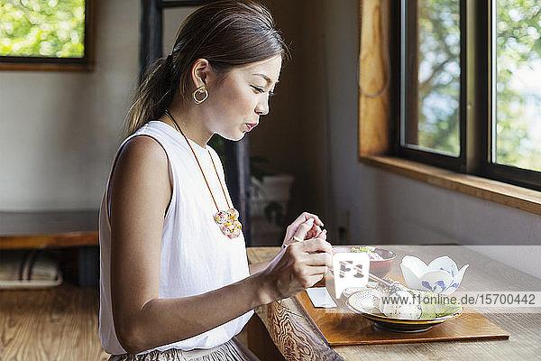 Japanerin  die an einem Tisch in einem japanischen Restaurant sitzt und isst.