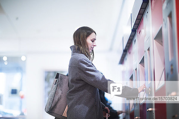 Young woman at ticket machine in train terminal