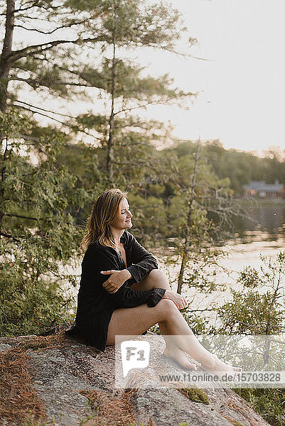 Woman relaxing on boulder by lake  Bobcaygeon  Ontario  Canada