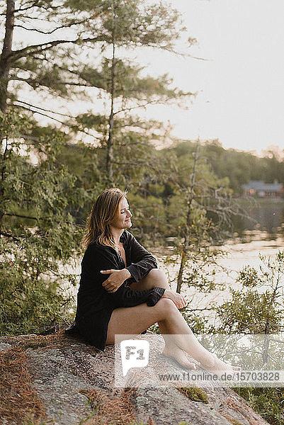Frau entspannt sich auf einem Felsbrocken am See  Bobcaygeon  Ontario  Kanada