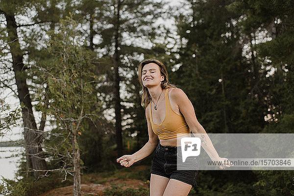 Tanzende Frau mit geschlossenen Augen im Wald