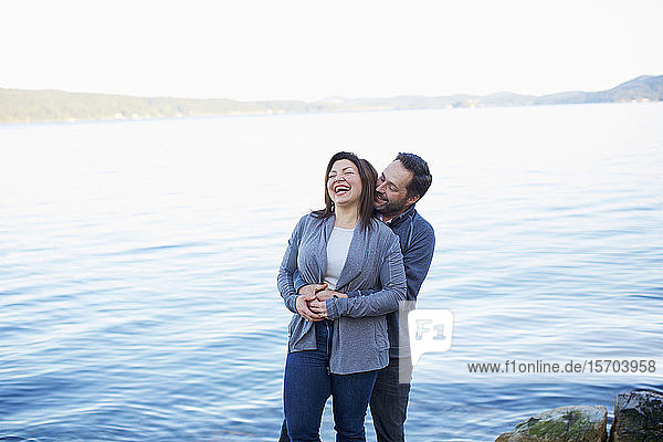 Happy  affectionate couple laughing and hugging at lake