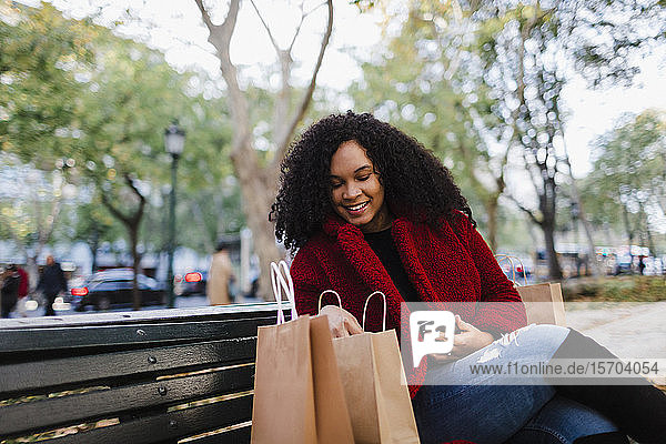 Smiling young woman looking in shopping bags on park bench
