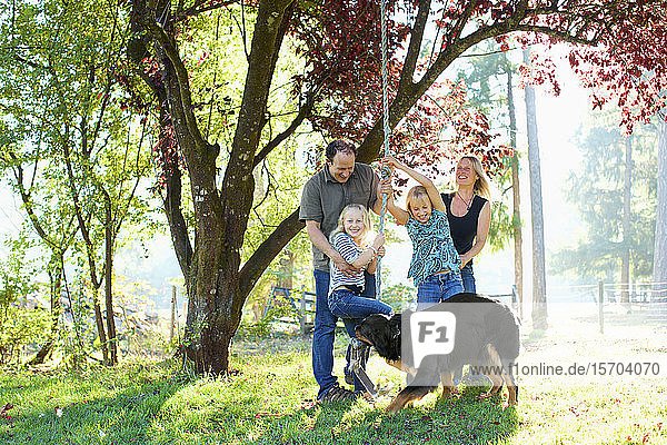 Happy family with dog playing on rope swing in sunny autumn park