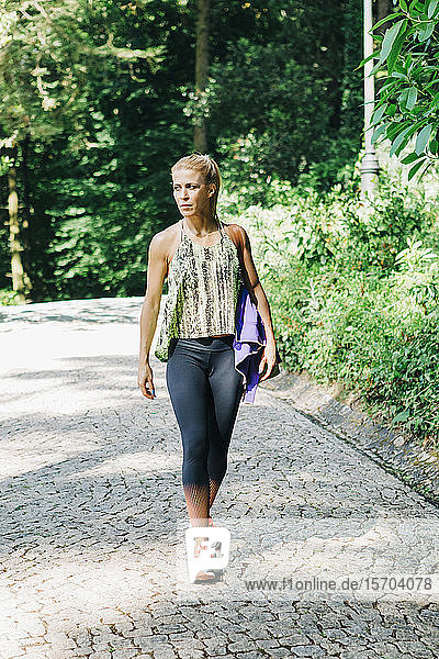 Fit female personal trainer walking on cobblestone path in park
