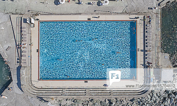 Aerial view from above tourists swimming in sunny  blue resort swimming pool  Genoa  Liguria  Italy