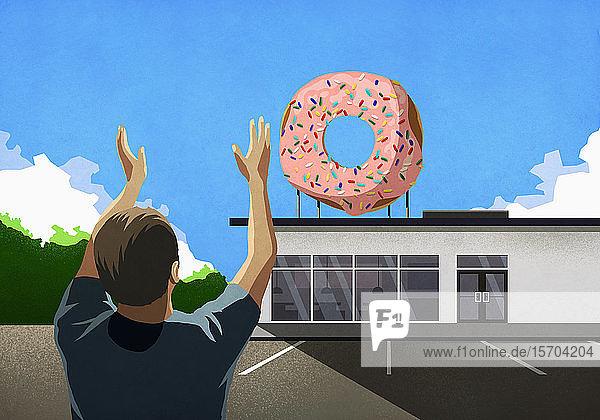 Mann mit erhobenen Armen blickt auf rosa Donut auf der Spitze der Bäckerei