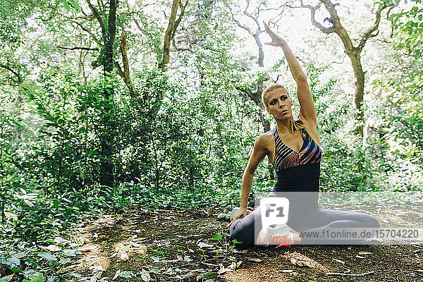 Fit female personal trainer stretching in forest