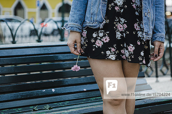 Cropped image woman in floral dress holding flower at park bench
