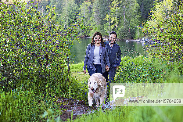 Happy couple with dog hiking along lush green lakeside  Mill Bay  British Columbia  Canada