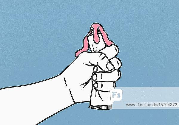 Die Hand drückt die Zahnpastatube aus