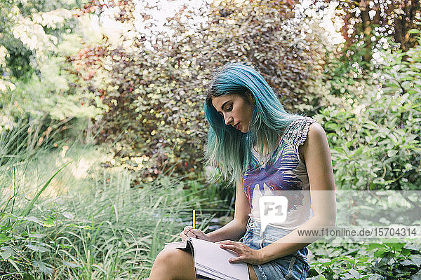 Young woman with blue hair writing in journal in park