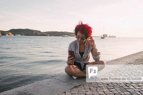 Woman with red hair listening to music with headphones and smart phone at waterfront  Portugal