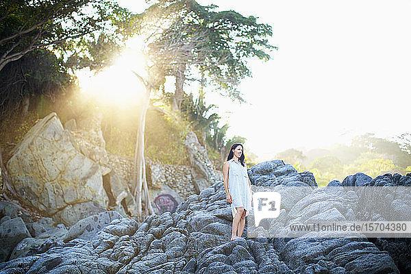 Serene woman standing on rocks under sunny tree  Sayulita  Nayarit  Mexico