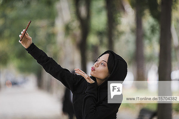Confident  playful woman taking selfie with camera phone  blowing a kiss