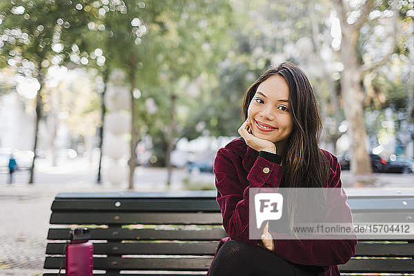 Portrait happy woman on park bench