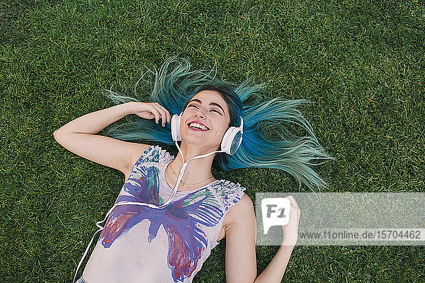 Happy  carefree young woman with blue hair listening to music with headphones  laying in grass