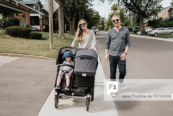 Couple taking toddler in baby carriage for walk in neighbourhood