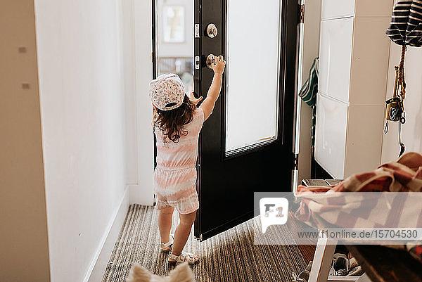 Toddler opening front door of house
