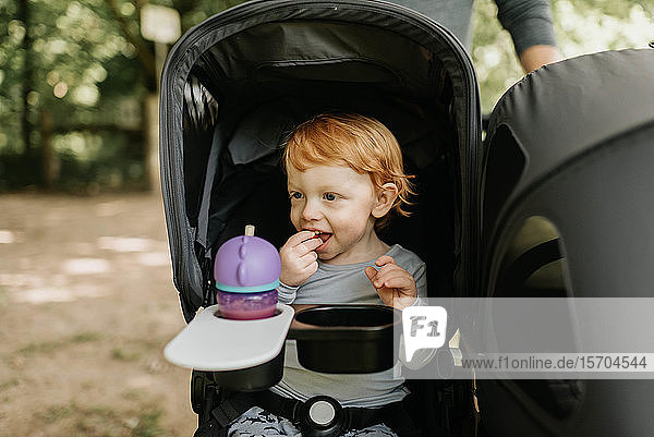Toddler eating in baby carriage