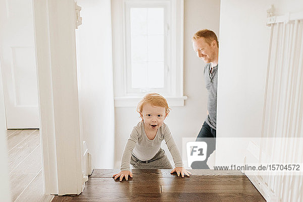 Father following son crawling up stairway in house