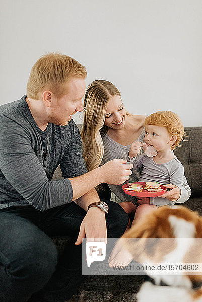 Couple watching son eating sandwich on mother's lap