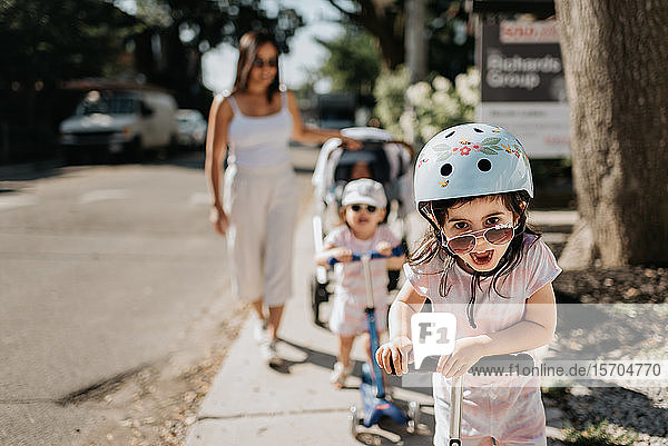 Mother and daughters playing push scooter in neighbourhood