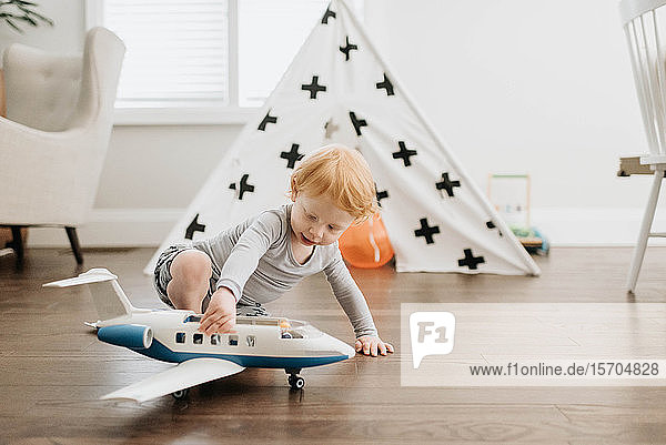 Toddler playing with toy aeroplane in living room