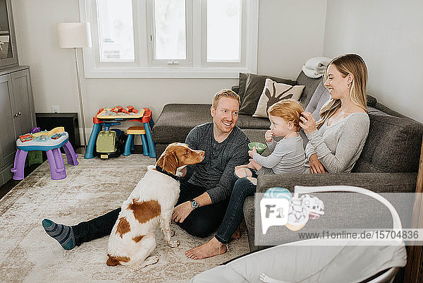 Family of three and pet dog relaxing in living room