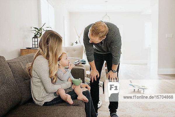 Vater spricht mit Sohn beim Essen auf dem Schoss der Mutter im Wohnzimmer