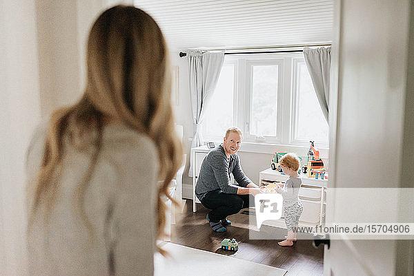 Ehepaar redet  während der Vater mit dem Sohn im Schlafzimmer spielt
