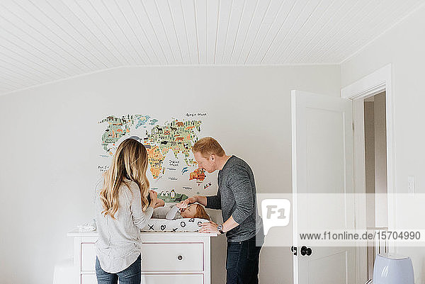 Couple changing toddler's diaper on changing table