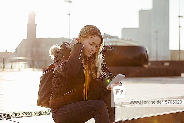 Teenager-Mädchen benutzt Smartphone  während sie an einem sonnigen Tag auf einer Treppe sitzt