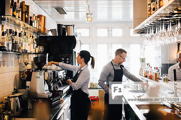 Male and female coworkers working in kitchen at restaurant