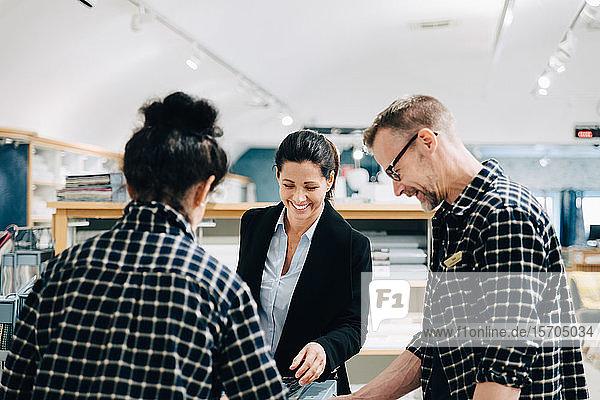 Männliche und weibliche Arbeitnehmer  die weiblichen Kunden im Laden helfen
