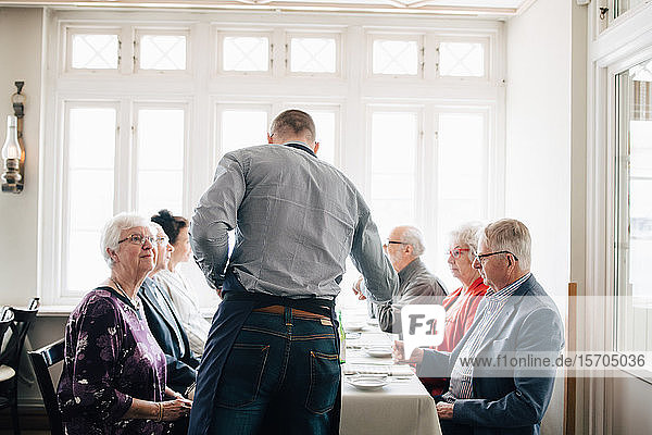 Owner standing by senior friends table in restaurant