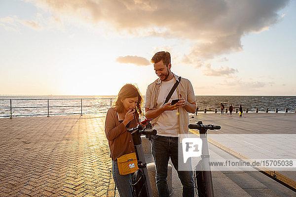 Paar mit elektrischen Schubrollern,  die ein Mobiltelefon benutzen,  während sie bei Sonnenuntergang auf der Promenade stehen