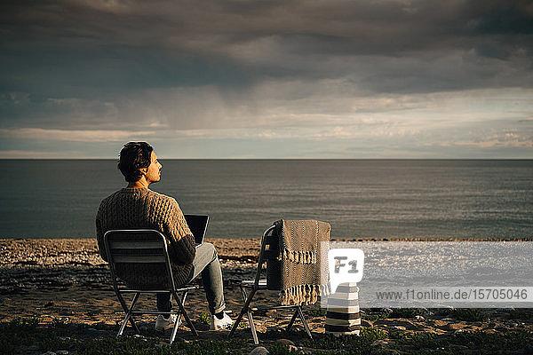 Nachdenklicher Mann benutzt Laptop  während er am Strand vor bewölktem Himmel sitzt