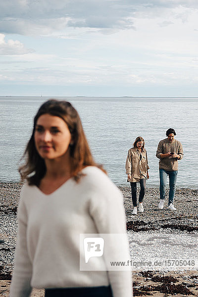 Friends talking while walking on sea shore with woman in foreground