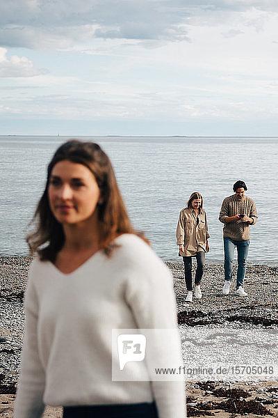 Freunde unterhalten sich beim Spaziergang am Meeresufer mit der Frau im Vordergrund