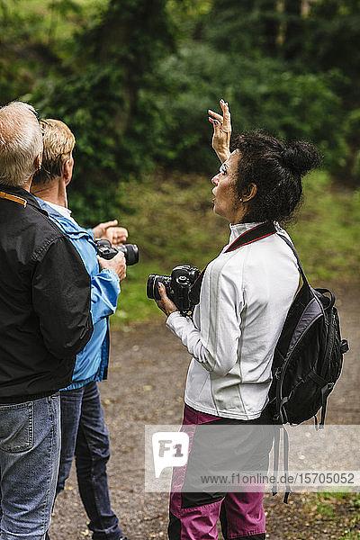 Weibliche Ausbilderin gestikuliert  während sie älteren Männern während eines Fotokurses Erklärungen gibt