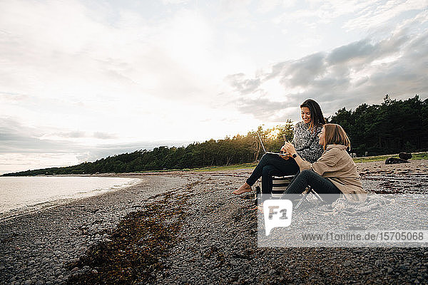 Freundinnen  die bei Sonnenuntergang am Strand zusammensitzen und auf ihr Handy schauen