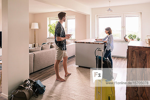 Woman filling form while man using phone at house rental during staycation