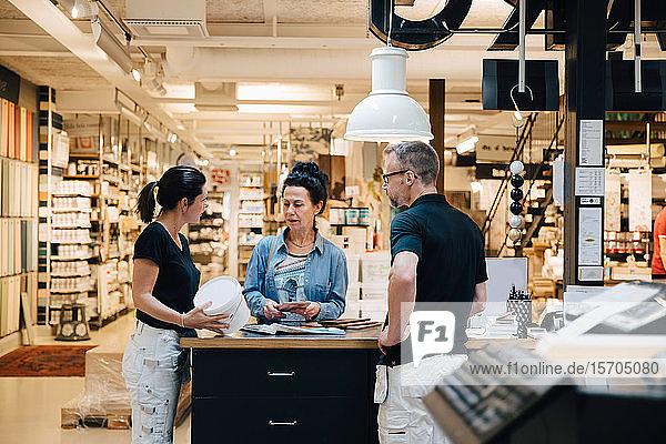 Weiblicher Kunde im Gespräch mit Verkaufsmitarbeitern im Baumarkt