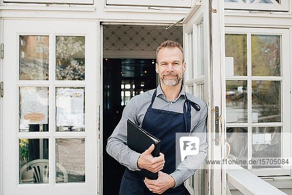 Porträt eines an der Tür stehenden Restaurantbesitzers