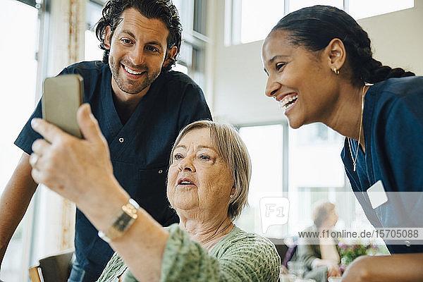 Ältere Frau  die mit lächelnden Krankenschwestern und Krankenpflegern im Altenheim Selbsthilfe betreibt